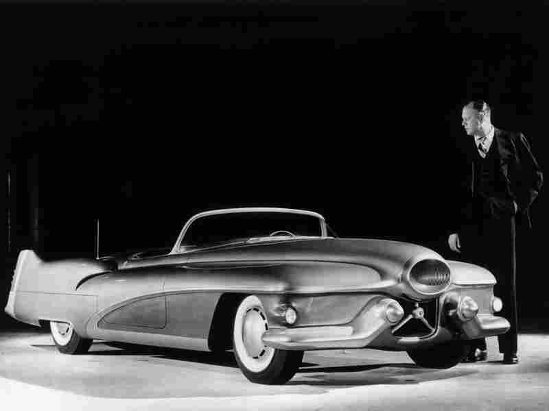 Designer Harley J. Earl of General Motors examining a full scale model of the Buick Le Sabre, a prototype sports car which was used to test design features for other vehicles. Earl is credited for helping to design a variety of cars in stylish new colors that would change every year, which would later be known as the annual model change.