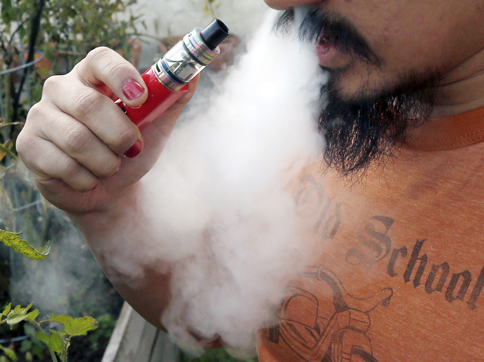 A man vapes with an electronic cigarette. On Thursday, the CDC said lung-injury patients reported using 152 different THC-containing product brands. (Jim Mone/AP)