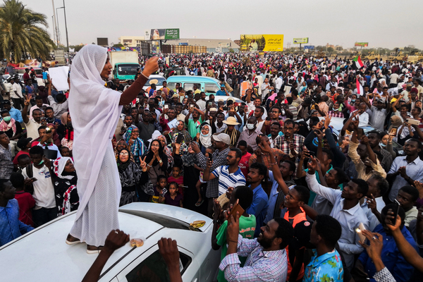 """Standing on a white car and wearing a traditional white thobe, Sudanese student Alaa Salah led protest chants against longtime dictator President Omar al-Bashir in Khartoum in April 2019. A social media post showing a photo of Salah went viral, and she was dubbed Sudan's """"Lady Liberty."""" Sudan's military ousted Bashir that same month."""