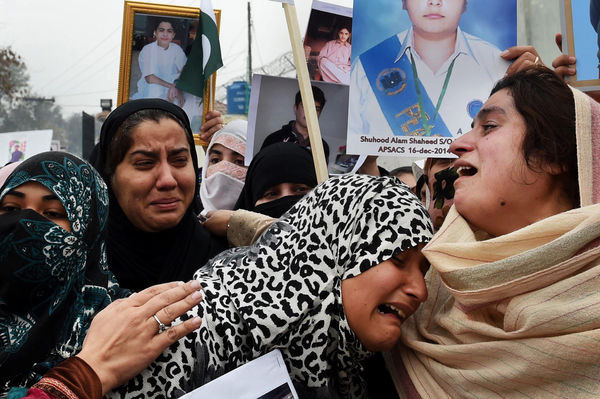 Relatives of more than 100 Pakistani schoolchildren killed in a December 2014 Taliban attack in Peshawar weep during a protest over delays in an investigation of the massacre in February 2015.