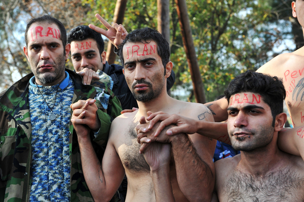 Their lips sewn shut in protest against limits on their movement, asylum-seekers from Iran wait to cross from Greece into Macedonia at the border near Idomeni, Greece, in November 2015.