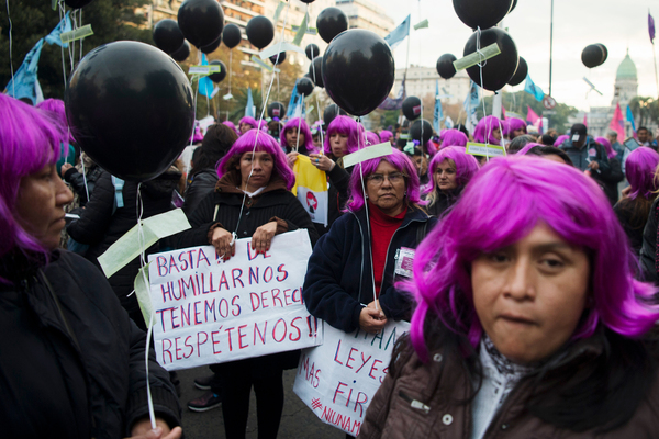 """Demonstrators wearing purple wigs representing the """"Ni Una Menos"""" (Not One [Woman] Less) movement hold signs saying """"Enough humiliation, we have rights, respect us"""" during a June 2016 protest against violence against women in Buenos Aires, Argentina."""
