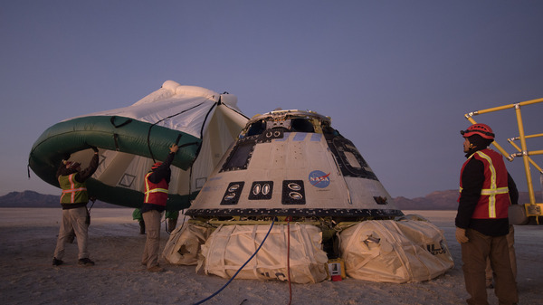 Boeing, NASA, and U.S. Army personnel work around the Boeing Starliner spacecraft shortly after it landed in White Sands, N.M., Sunday.