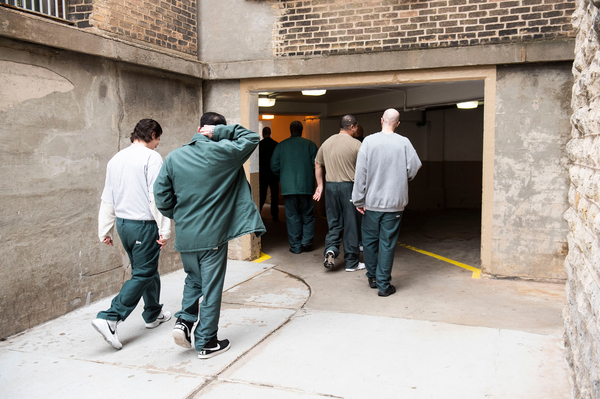 """Prisoners pass through a courtyard at Waupun Correctional Institution. Officials in some prison towns have come up with creative ways to avoid forming voting districts made up primarily of prisoners. But in many others, political lines are drawn around prisons in a way that critics deride as """"prison gerrymandering."""""""