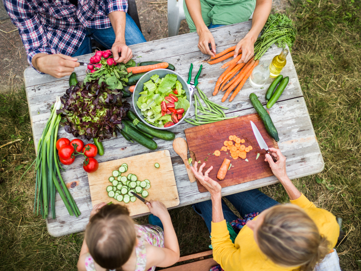 Family preparing fresh salad in a garden
