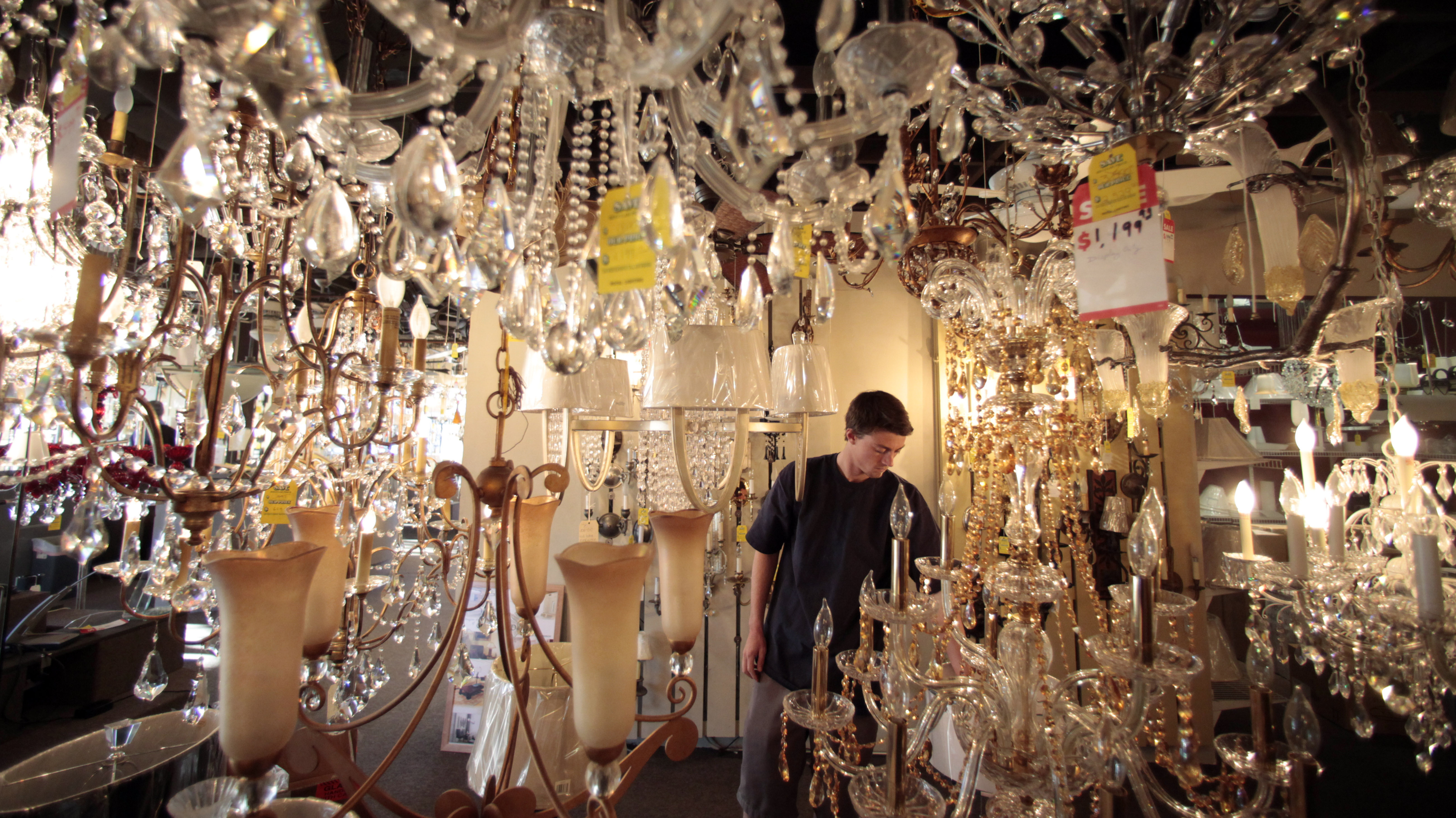Jack George, an employee at Royal Lighting, looks at chandeliers using incandescent light bulbs at the store in Los Angeles. A federal judge is allowing California to enforce updated efficiency standards that will affect such specialty lightbulbs.