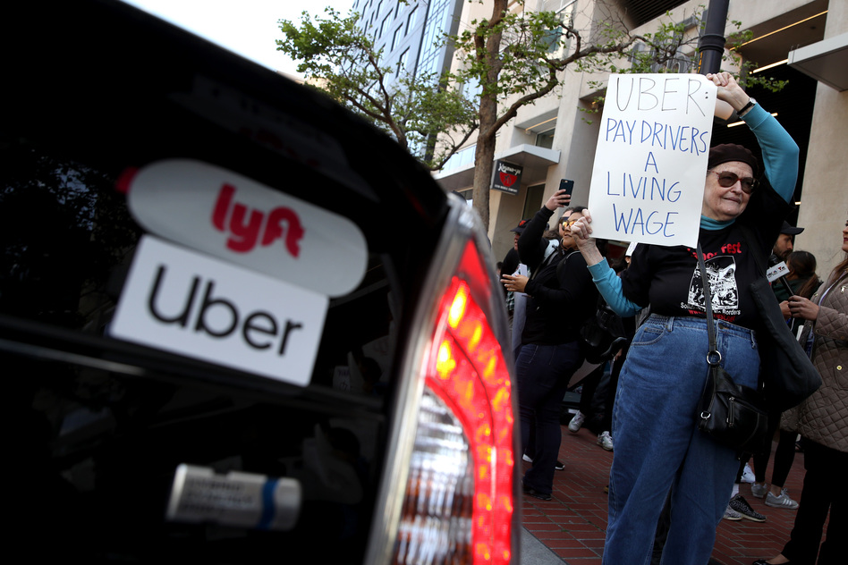 A supporter of ride-hail drivers holds a sign during a protest in front of Uber headquarters on May 8 in San Francisco. A new law in California aims to change how gig economy and other contract workers are classified. (Justin Sullivan/Getty Images)