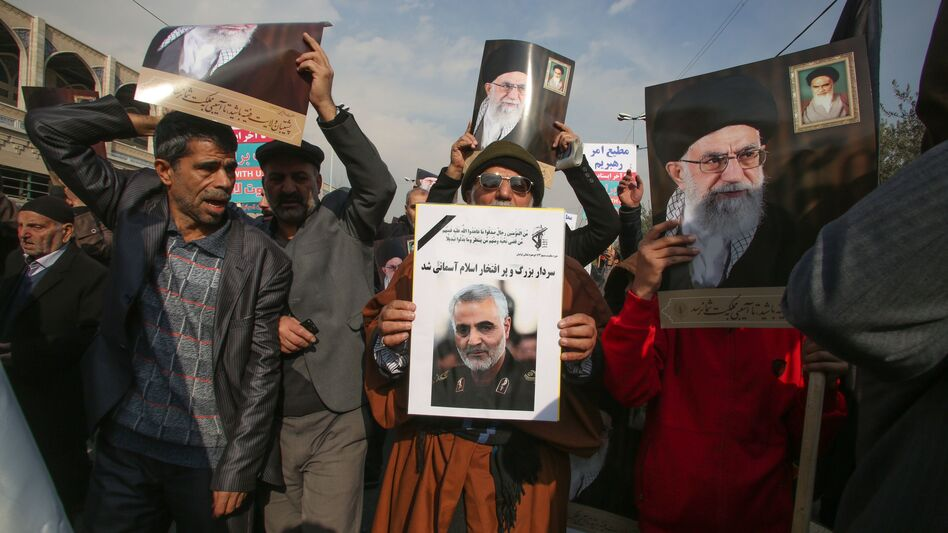 Iranian demonstrators hold posters of slain Maj. Gen. Qassem Soleimani (center) and the country's supreme leader, Ayatollah Ali Khamenei, during a rally Friday in the capital, Tehran. The U.S. strike on the military leader in Baghdad has elicited warnings of retaliation from Iran. (Atta Kenare/AFP via Getty Images)