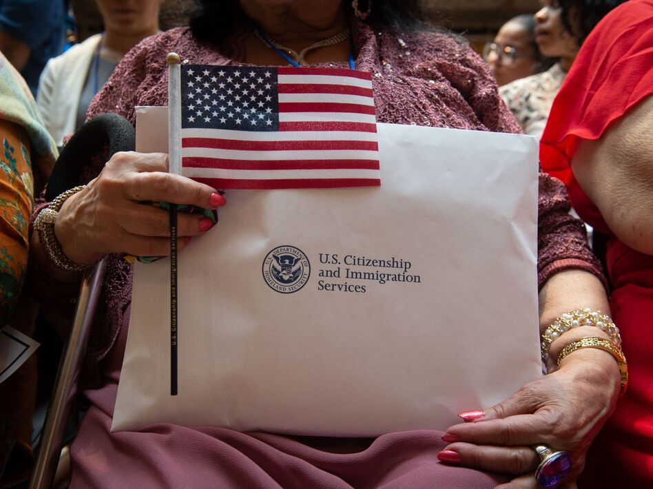 A newly sworn-in U.S. citizen holds the U.S. flag and paperwork during a 2018 naturalization ceremony in New York City. The Department of Homeland Security has agreed to share its records with the U.S. Census Bureau to help produce data about the U.S. citizenship status of every person living in the country, as ordered by President Trump. (Bryan R. Smith/AFP via Getty Images)
