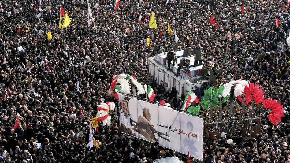 During a funeral procession at Revolution Square in Tehran on Monday, crowds surround the coffins of Iranian Maj. Gen. Qassem Soleimani and others killed in Iraq by a U.S. drone strike. (Ebrahim Noroozi/AP)