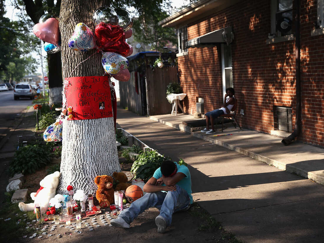 CHICAGO, IL - JULY 06: A teenage boy grieves next to a makeshift memorial at the site where Ashley Hardmon was shot and killed on July 4, 2013 in Chicago, Illinois. (Photo by Scott Olson/Getty Images)