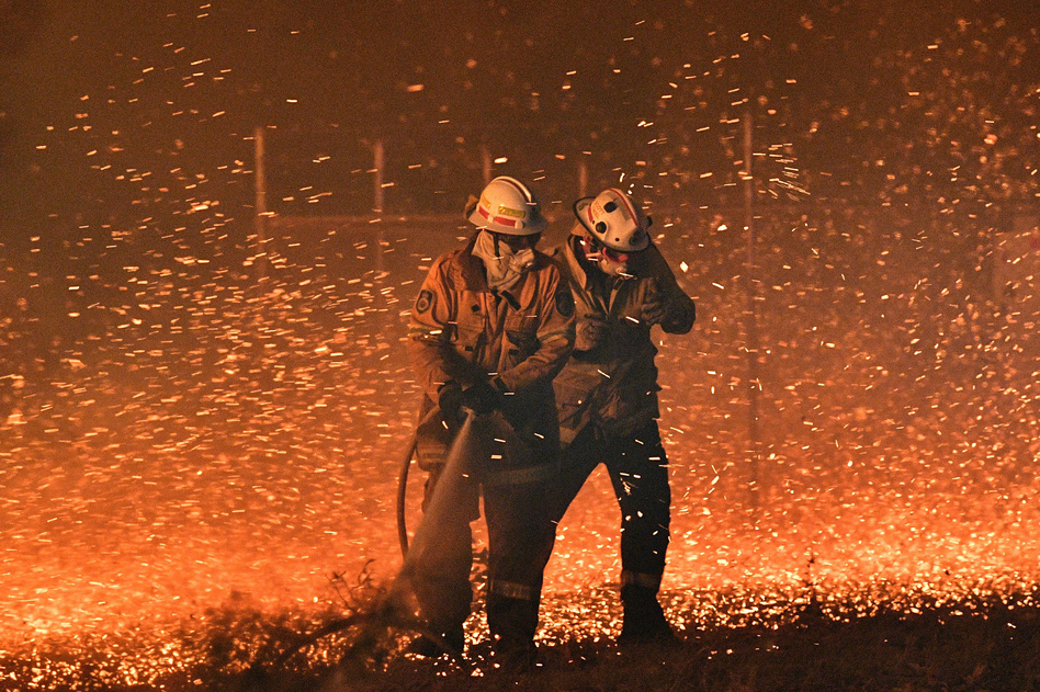 Firefighters struggle to protect homes from the embers generated by bushfires near the town of Nowra in New South Wales, Australia. (Saeed Khan/AFP via Getty Images)