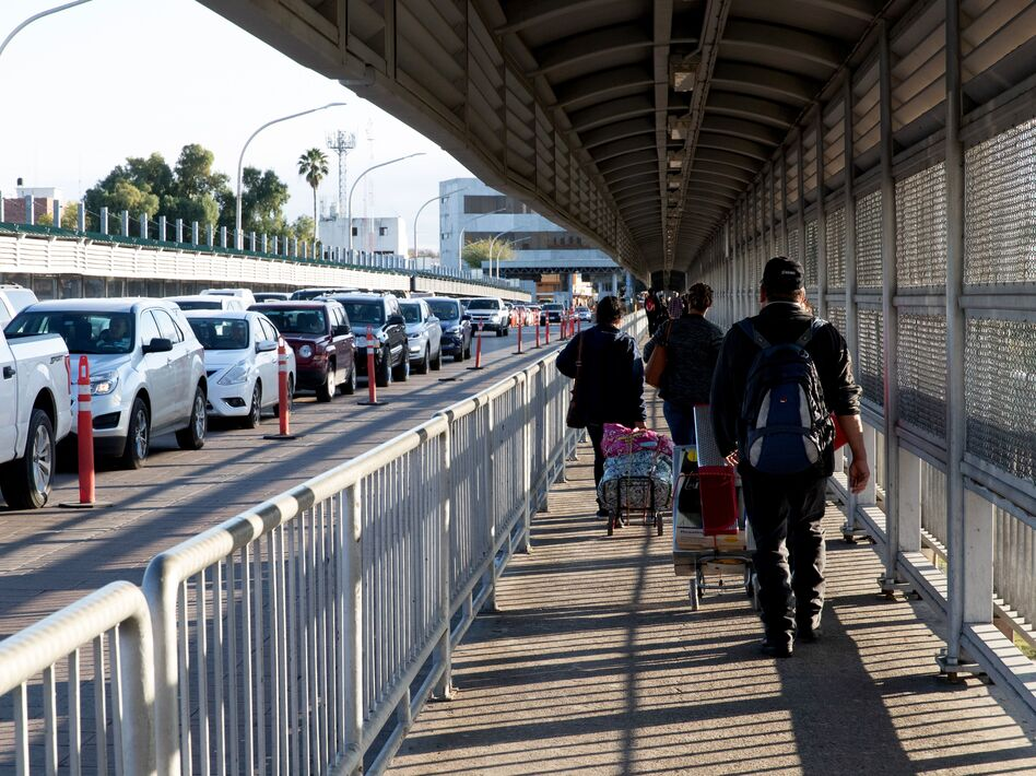 People walk and drive across a bridge on the U.S.-Mexico border in Laredo, Texas. Thousands of people cross back and forth every day, in cars or on foot. (Suzanne Cordeiro/AFP via Getty Images)