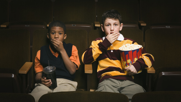 Two boys are surprised in a movie theater.