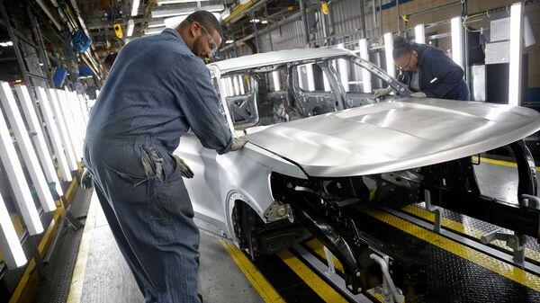 Workers assemble cars at Ford