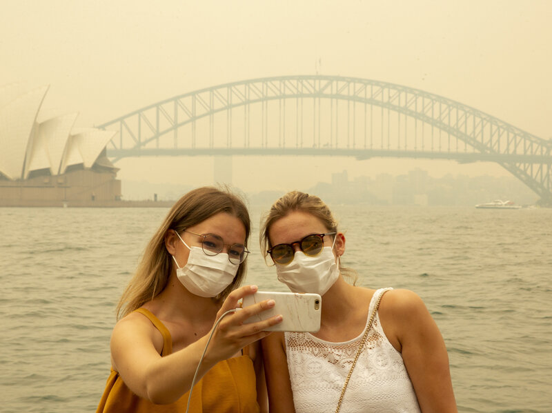 Visitors, wearing face veils because of overwhelming smoke, take a selfie at Sydney Harbor on Dec. 19, 2019. As updates on Australia's out of control fires spreads far and wide, less visitors are landing in the nation.