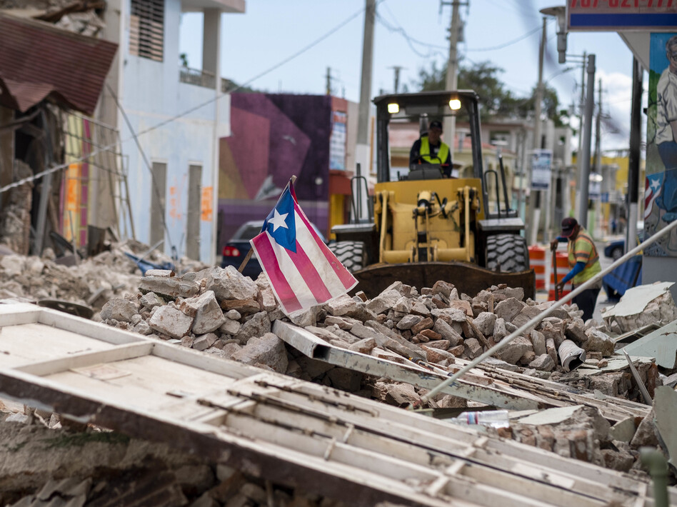 A Puerto Rican flag waves on top of a pile of rubble as debris is removed from a main road in Guánica. (Ricardo Arduengo  /AFP via Getty Images)