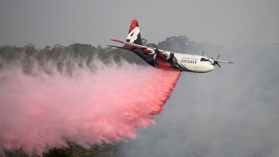 A New South Wales Rural Fire Service large air tanker drops fire retardant on the Morton Fire burning in bushland close to homes at Penrose, south of Sydney, on Friday. (Dan Himbrechts/AAP Image via Reuters)