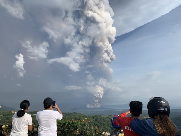 People take photos of the Taal Volcano from the vantage point of the town of Tagaytay in Cavite Province, southwest of Manila on Sunday.