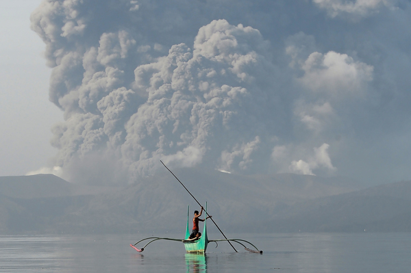 A boy who lives at the foot of Taal paddles an outrigger canoe while the volcano spews ash Monday.
