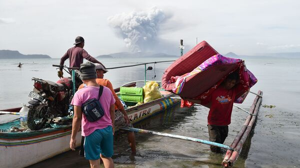 Residents who were living at the foot of Taal Volcano unload their belongings from an outrigger canoe while the volcano spews ash as seen from Tanauan town in Batangas Province, south of Manila, on Monday.