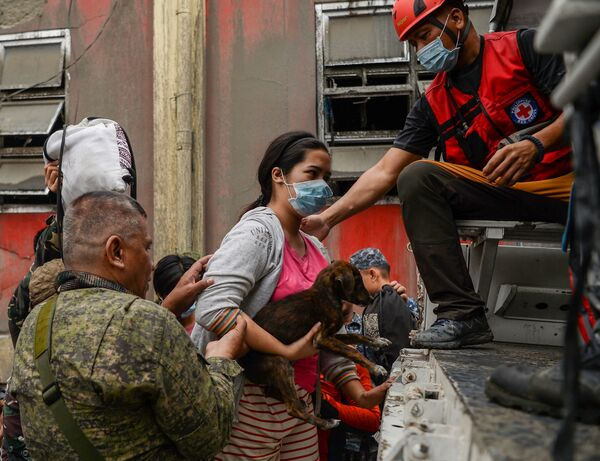 Rescue workers help a resident and her dog onto a truck as they evacuate to a safe area in Talisay town on Monday.