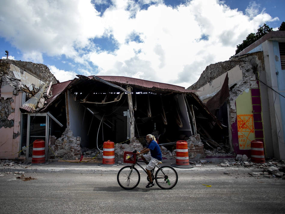 A cyclist rides past a destroyed building in Guanica, Puerto Rico. The island was hit by a series of earthquakes over the past couple of weeks, leading to a state of emergency, power outages and millions of dollars of damage. (Bloomberg/Bloomberg via Getty Images)