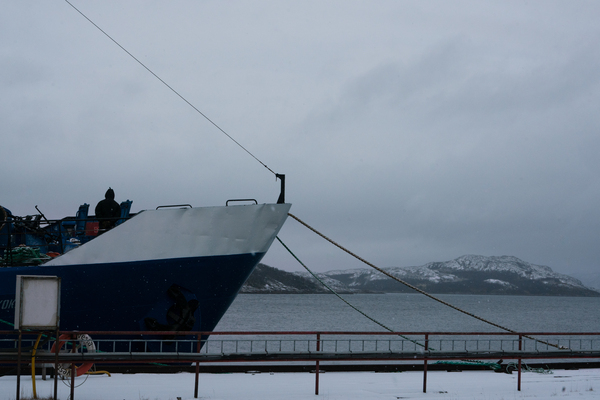 A view of a ship docked in the Kirkenes harbor.