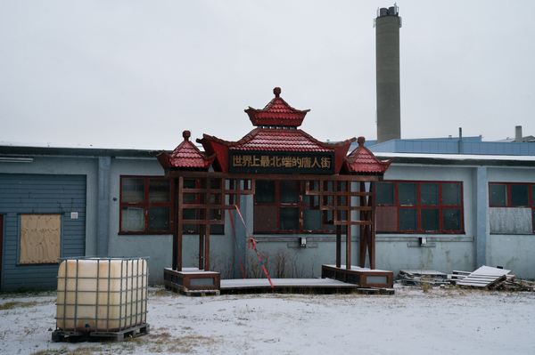 """A gate used for the town's annual winter festival, called """"Kirkenes, the world's northernmost Chinatown,"""" sits in an open lot."""