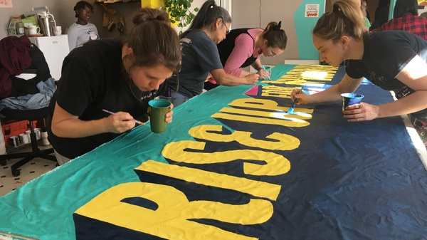 Volunteers paint a banner for the front of the demonstration. Organizers hosted the event to bring supporters together ahead of this year