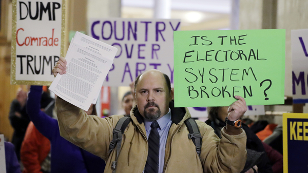 Brock Ervin holds a sign outside the Indiana House chamber at the Statehouse before the 11 representatives of the Electoral College gathered on Dec. 19, 2016, in Indianapolis.  The U.S. Supreme Court has agreed to hear two cases challenging state attempts to penalize electoral college delegates who fail to vote for the presidential candidate they were pledged to support.