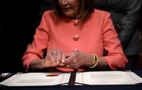 House Speaker Nancy Pelosi signs the articles of impeachment against President Trump at the Rayburn Room on Capitol Hill Jan. 15.