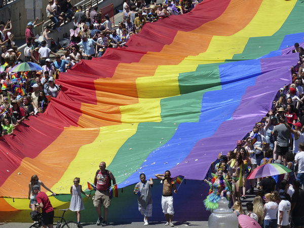 "Marchers raise a rainbow flag during the 2018 Pride parade in Salt Lake City. Late Tuesday, state regulators implemented a ban on ""conversion therapy"" aimed at changing the sexual orientation or gender identity of LGBTQ young people."