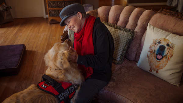 Peggy Gibson sits in her living room with her service dog, Rocky, in West Jefferson, N.C., last November. Gibson says Rocky, a diabetic alert dog, isn