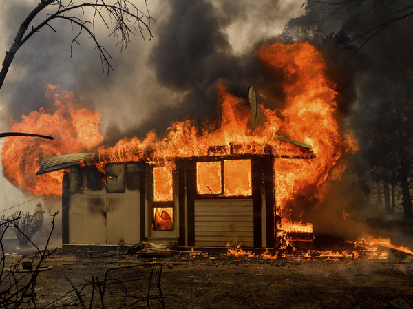 Flames from the Morton Fire consume a home near Bundanoon, New South Wales, Australia, on Thursday.