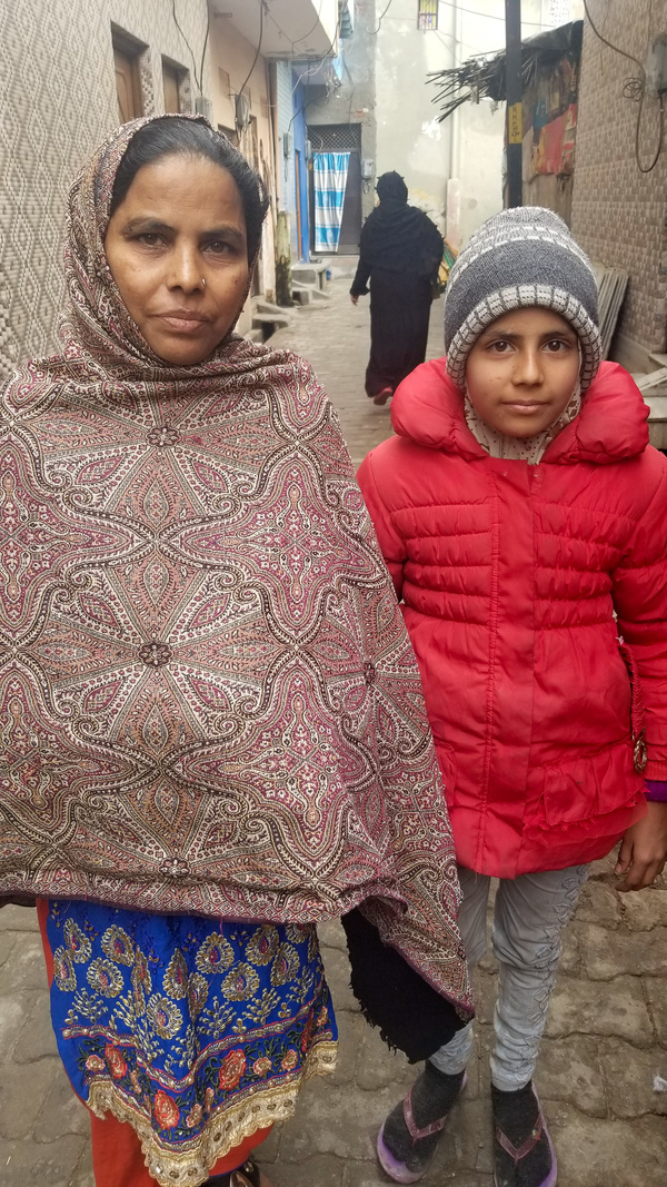 Bano (left), who goes by one name, and her daughter stand outside their home in Meerut. Another of Bano's children, 17-year-old Amjad, was wounded by police last month, and then arrested and charged with inciting violence. The family says he is innocent.