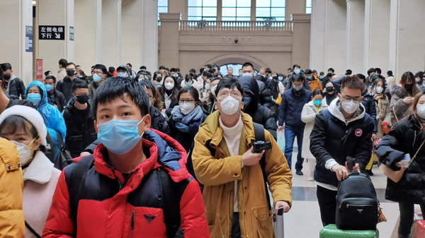 """People wear face masks as they wait at Hankou Railway Station on January 22, 2020 in Wuhan, China. A new infectious coronavirus known as """"2019-nCoV"""" was discovered in Wuhan last week."""