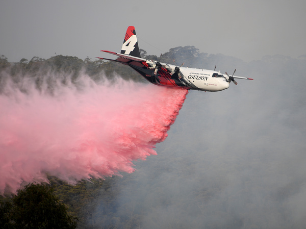 An air tanker operated by Canada-based Coulson Aviation drops fire retardant on the Morton Fire burning in bushland close to homes at Penrose, south of Sydney, Australia, earlier this month.