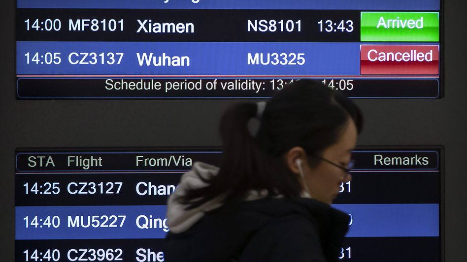 A traveler walks past a display board showing a canceled flight from Wuhan at Beijing Capital International Airport on Thursday. China closed off the city of more than 11 million in an unprecedented effort to try to contain a deadly new viral illness that has sickened hundreds and spread to other cities and countries during the Lunar New Year travel rush. (Mark Schiefelbein/AP)