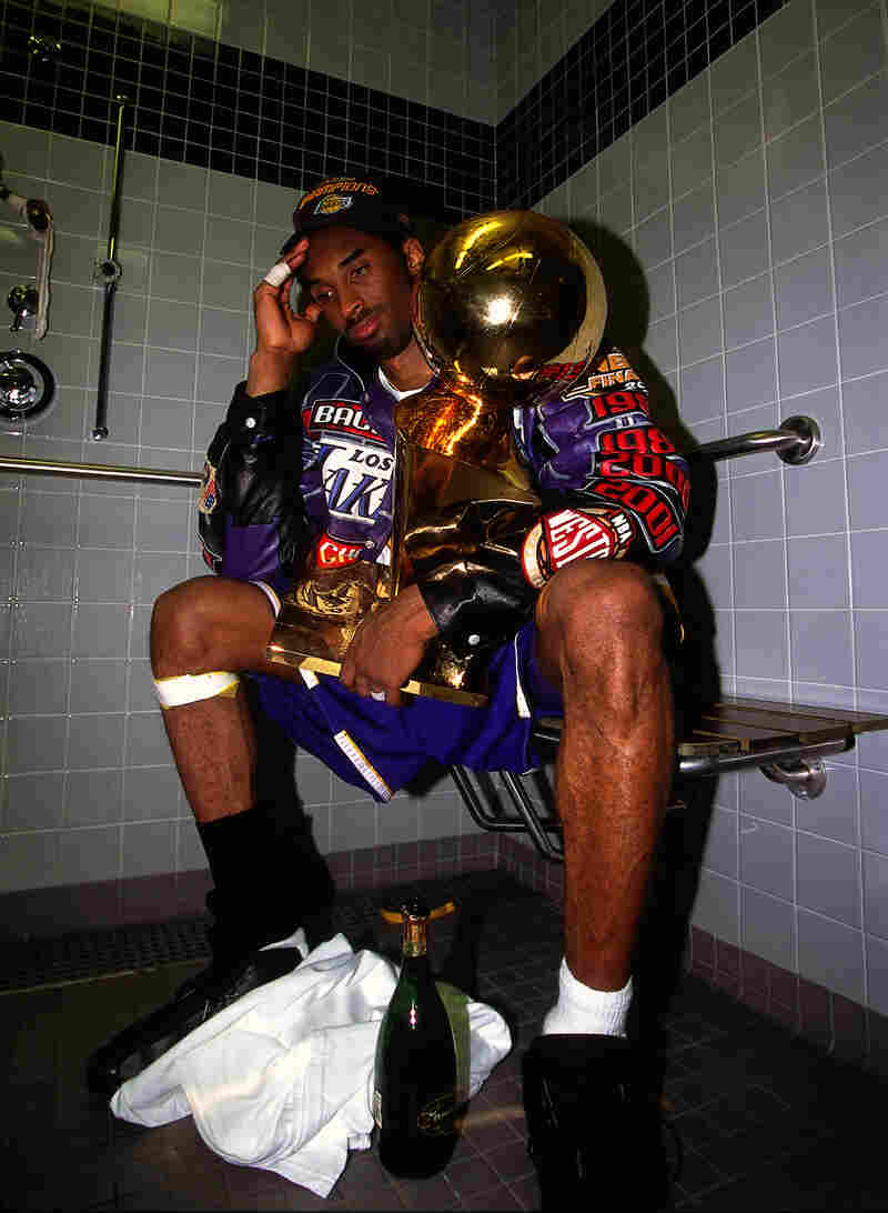 Bryant sits with the NBA Championship trophy after the Lakers defeated the Philadelphia 76ers to win the 2001 NBA title on June 15, 2001.