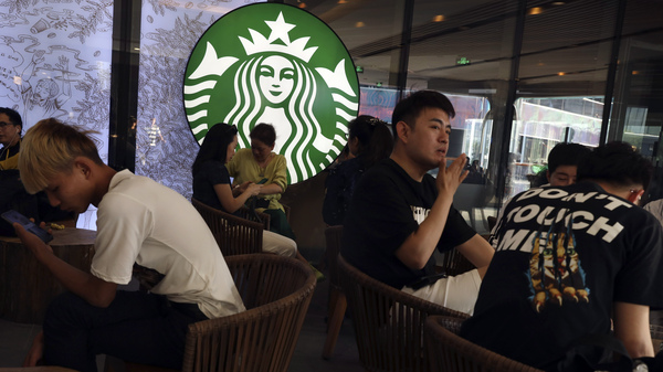 In a photo taken in May, customers enjoy their drinks at a Starbucks in Beijing. The U.S.-based coffee chain has decided to close more than half its stores in mainland China due to the coronavirus outbreak.
