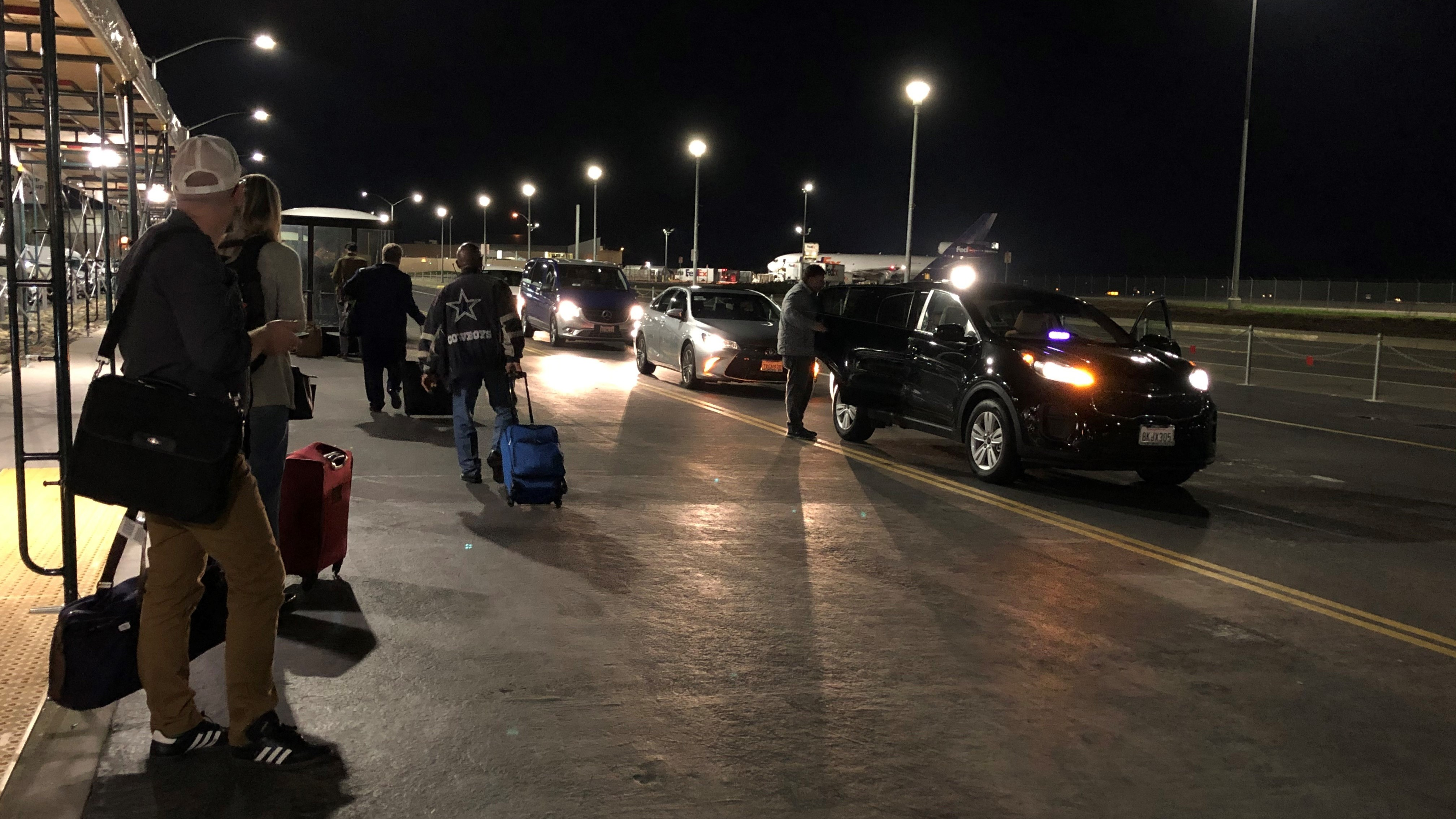 Travelers wait at the ride-share pickup location at Sacramento International Airport. Uber is allowing drivers at three California airports to set their own fares.