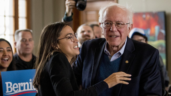 Sen. Bernie Sanders smiles as he is welcomed to the podium by Rep. Alexandria Ocasio-Cortez of New York during a campaign stop in Perry, Iowa.