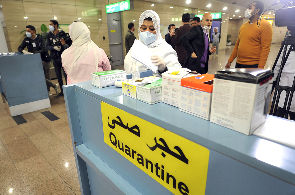 Employees of the Egyptian Quarantine Authority prepare to scan the body temperature of incoming travelers at Cairo International Airport. (AFP via Getty Images)