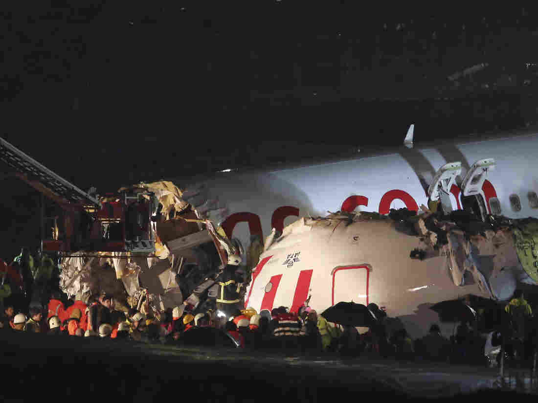 Rescue members and firefighters work after a plane skidded off the runway at Istanbul's Sabiha Gokcen Airport on Wednesday.