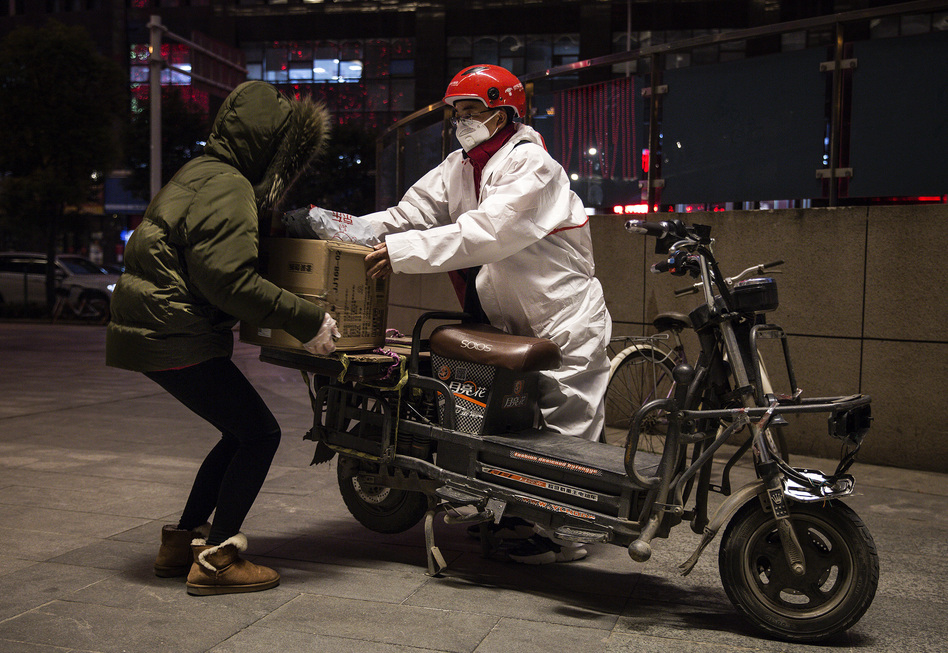 A delivery person wears a protective mask and suit as he delivers packages by bicycle on Saturday in Wuhan, China. (Getty Images)