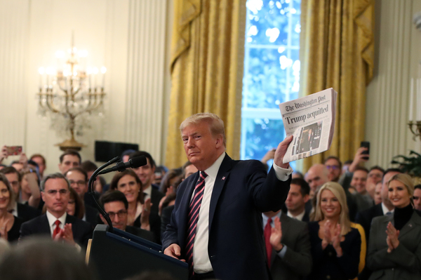 President Trump, surrounded by members of his administration and supporters, holds up a newspaper during remarks at the White House on Thursday.
