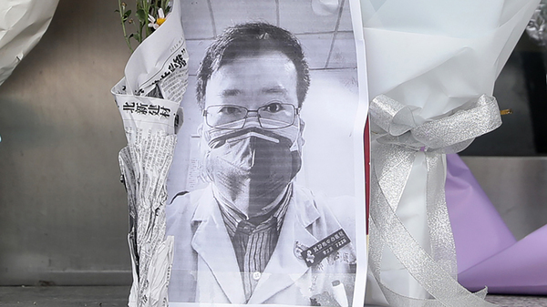 A photo of the late ophthalmologist Li Wenliang is seen with flower bouquets at the Houhu Branch of Wuhan Central Hospital in Wuhan, central China, on Friday. Li, who is being hailed for his efforts to alert the medical profession to the new virus,  died Friday after becoming infected.