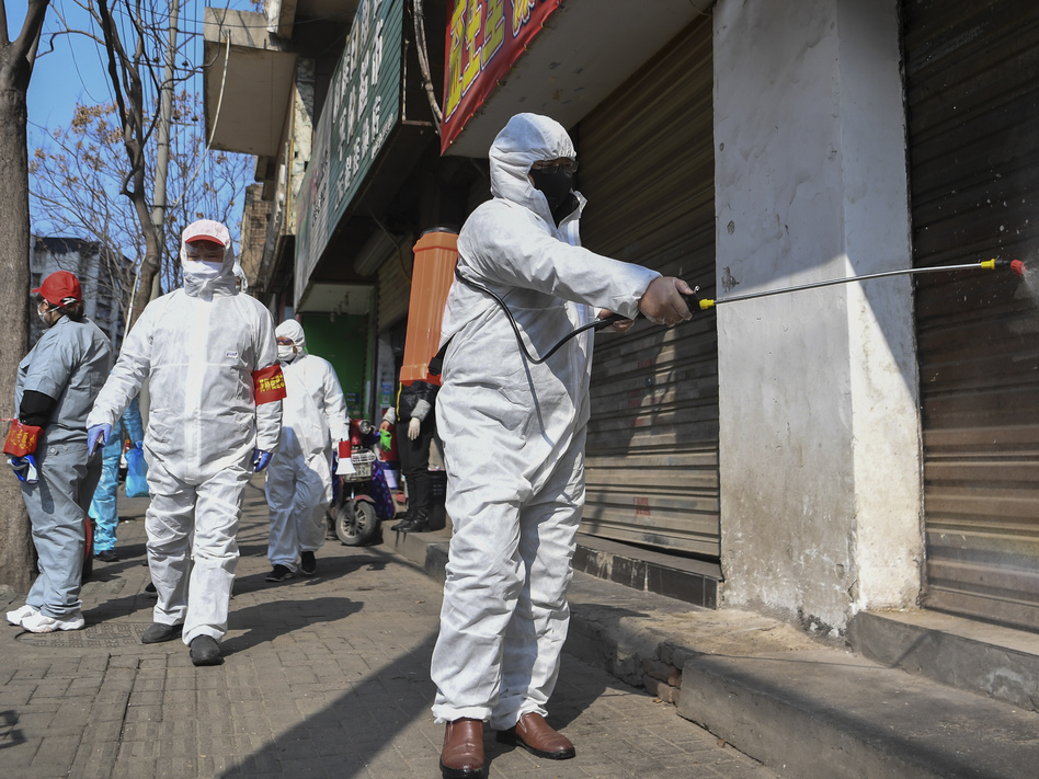 Workers disinfect closed shop lots following the coronavirus outbreak in Hubei, China, on Monday. Officials reported on Tuesday that the country's overall death toll had passed 1,000. (Cheng Min/AP)