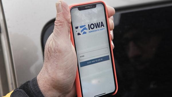 Precinct captain Carl Voss of Des Moines displays the Iowa Democratic Party caucus reporting app on his phone outside of the Iowa Democratic Party headquarters.